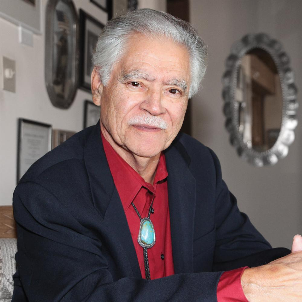 Portrait of Rudolfo Anaya, wearing a red shirt, in his home
