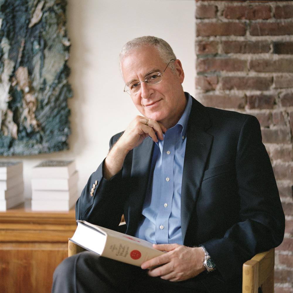 Ron Chernow, seated, with a book in his lap