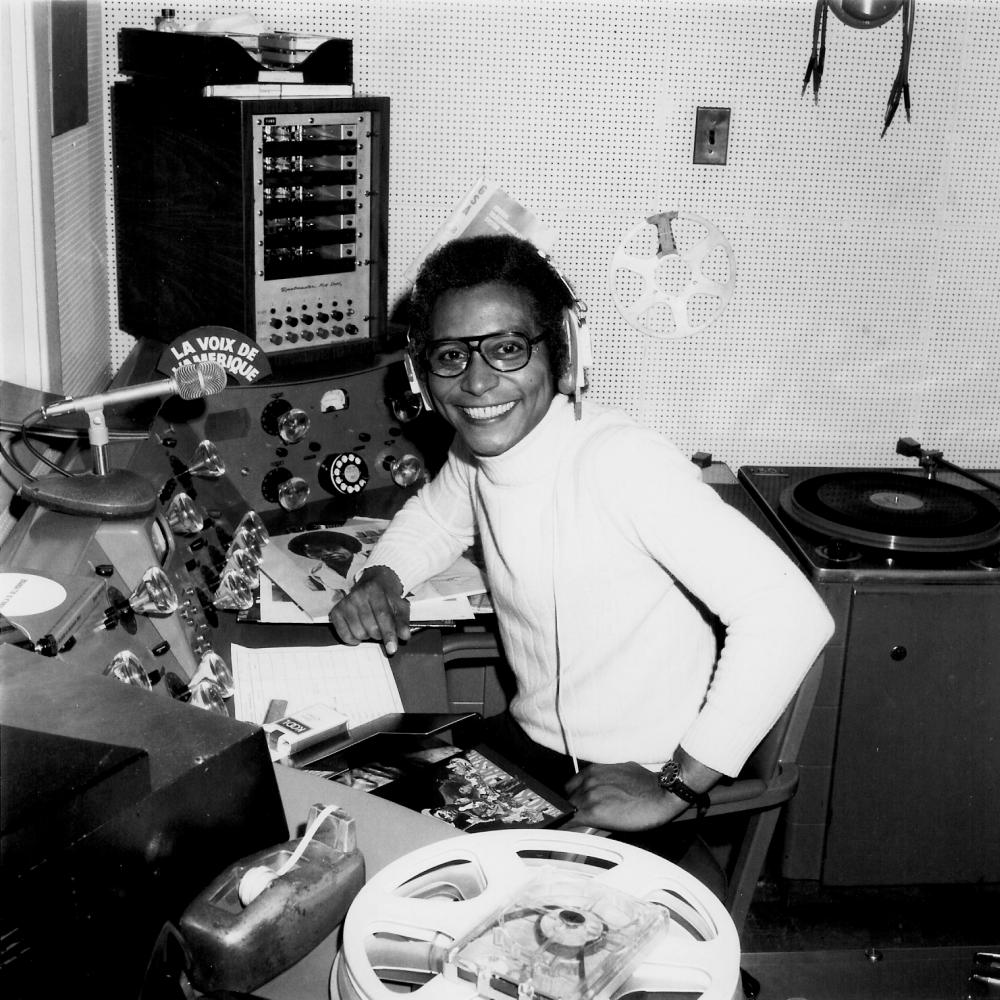 Collinet in a white turtleneck, sitting at a radio broadcasting panel with headphones on, smiling at the camera