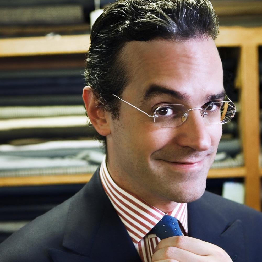 Anton, wearing rimless glasses and hair slicked back, adjusts his blue tie, worn with a red and white striped shirt and black blazer