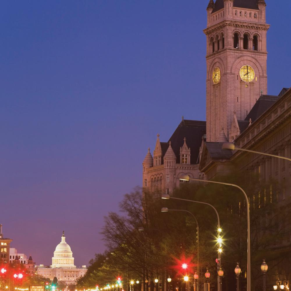 Photograph of clock tower, the United States capitol building at end of street