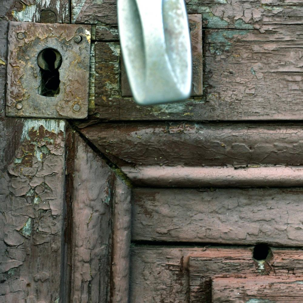 photograph of a wooden door with a bullet hole in it