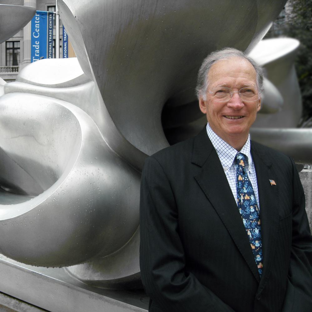 Photograph of man in suit leaning against a contemporary sculputre