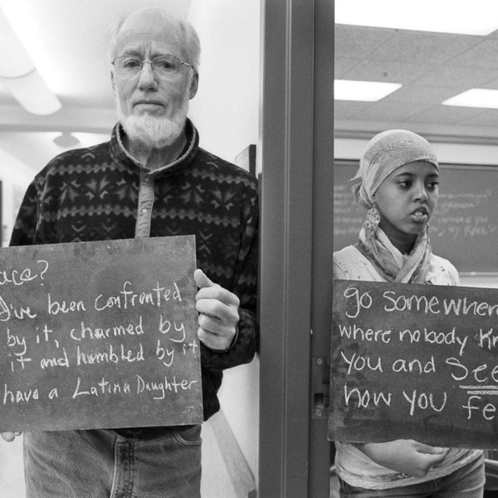 Black and white photo of two individuals holding signs that have provocative statements about race on them.