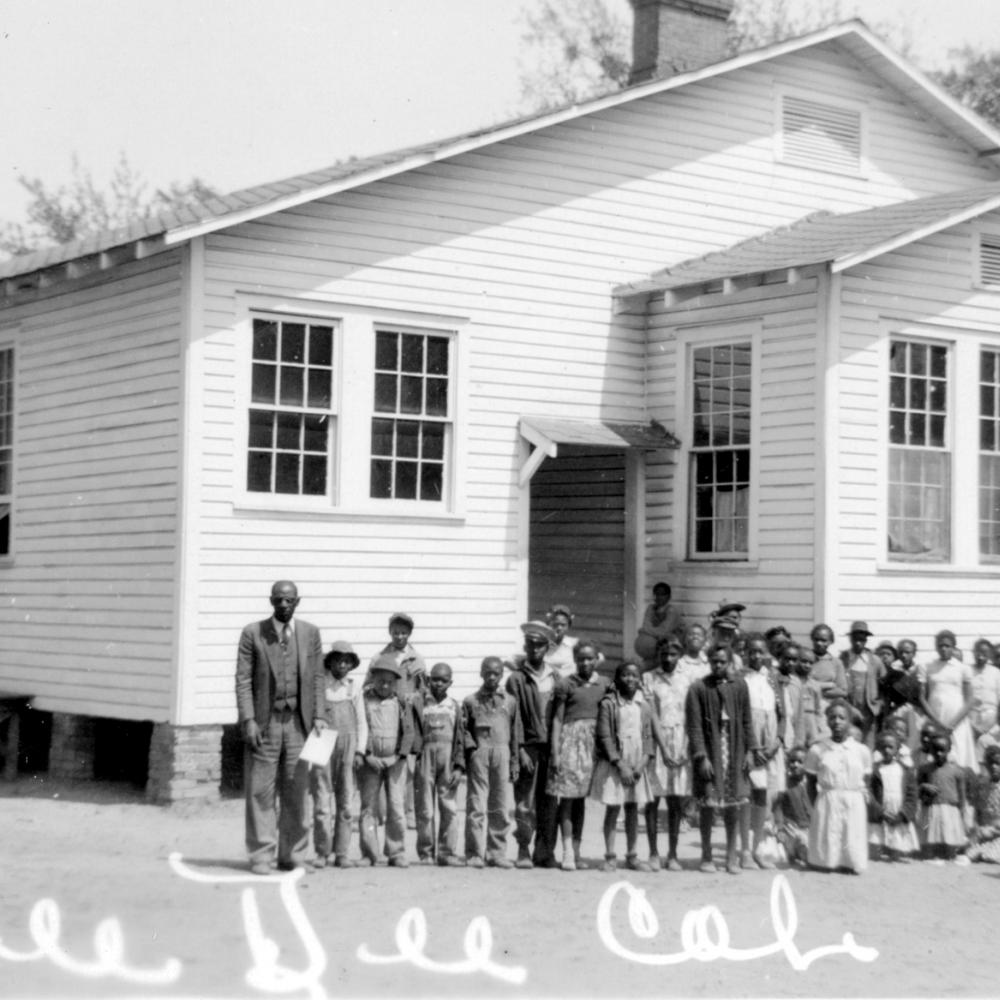 Black and white photo of African American students standing in front of a small white schoolhouse.