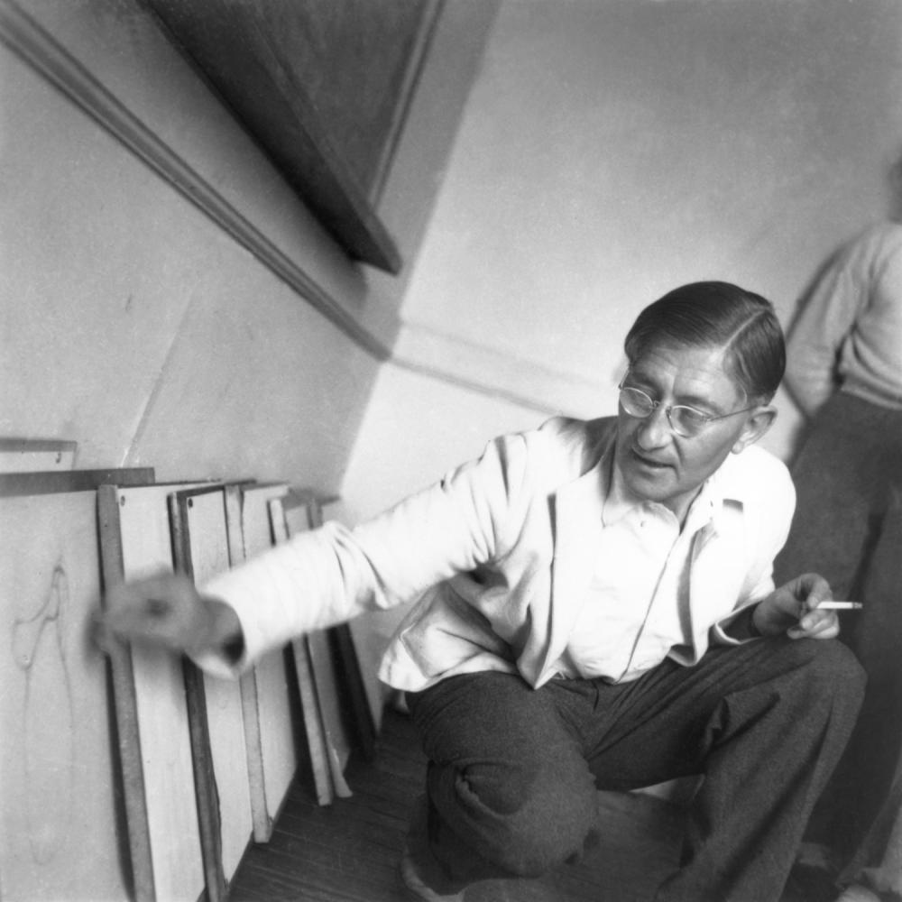 Albers holding a cigarette and kneeling in front of several diagrams