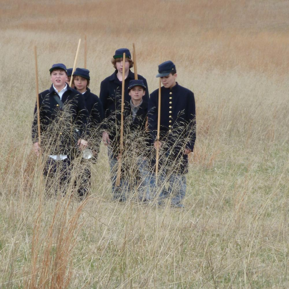 Color photo of a group of schoolboys re-enacting a Civil War march through a field.