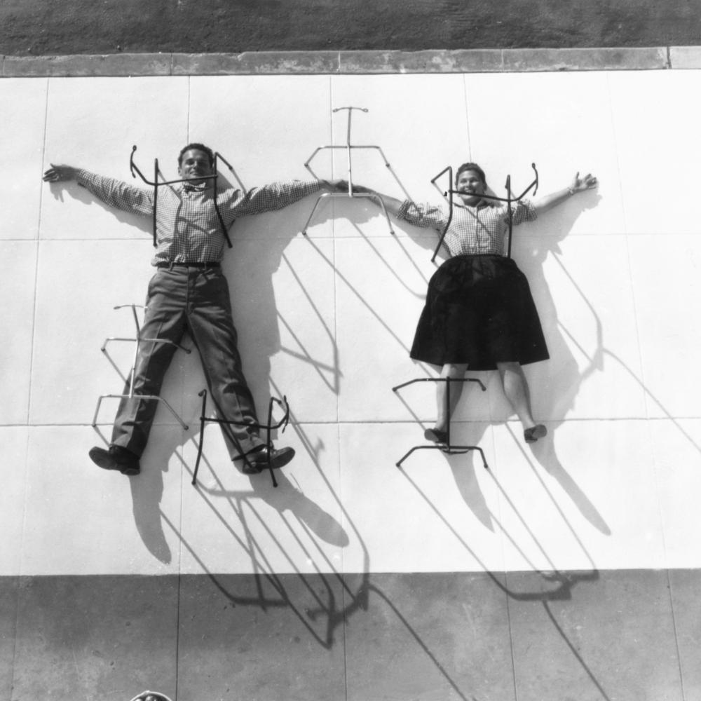 A man and a woman spread out in snow angel fashion over a concrete block, to which they are pinned by rods.