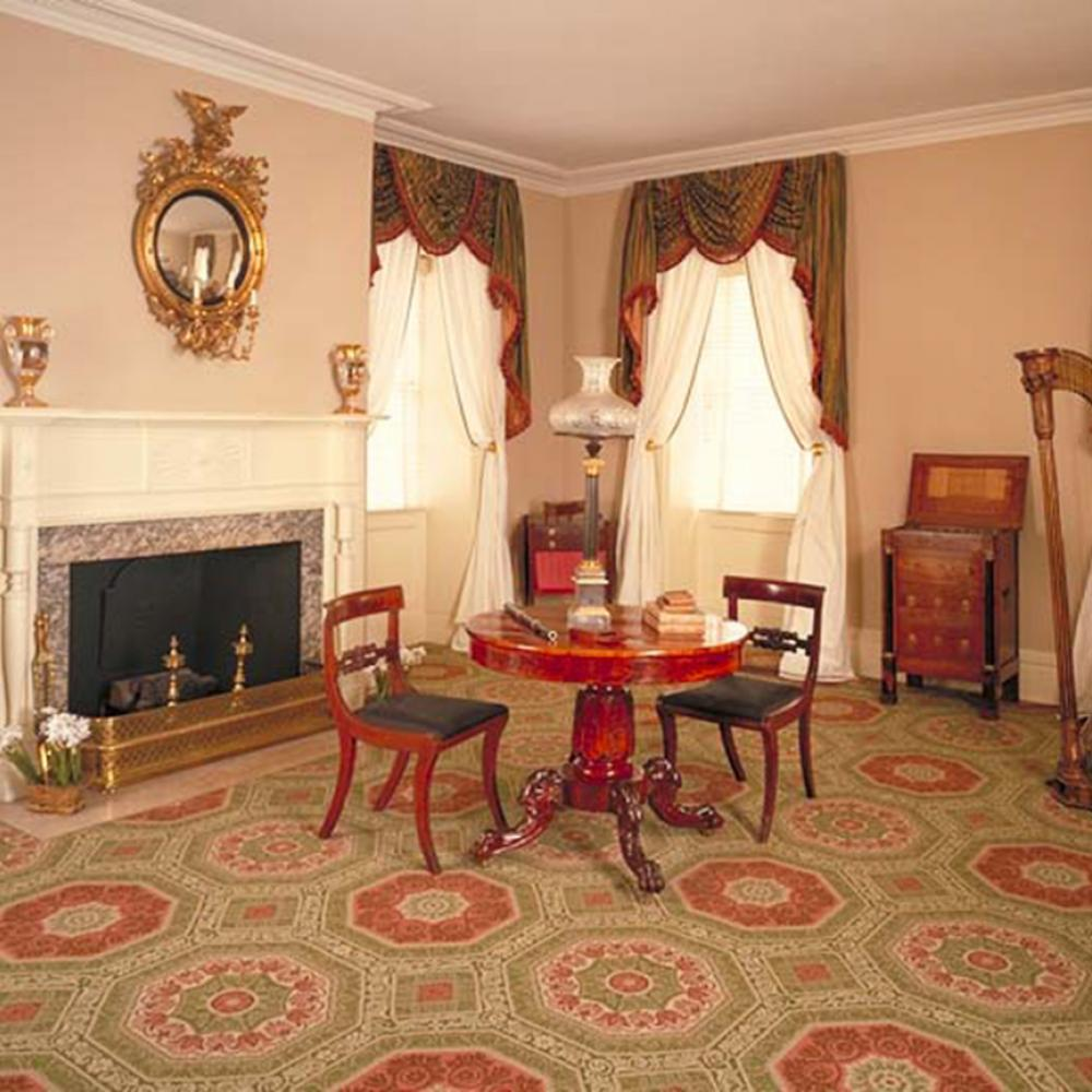 Color photo of an elegant parlor with a table and two chairs at its center.