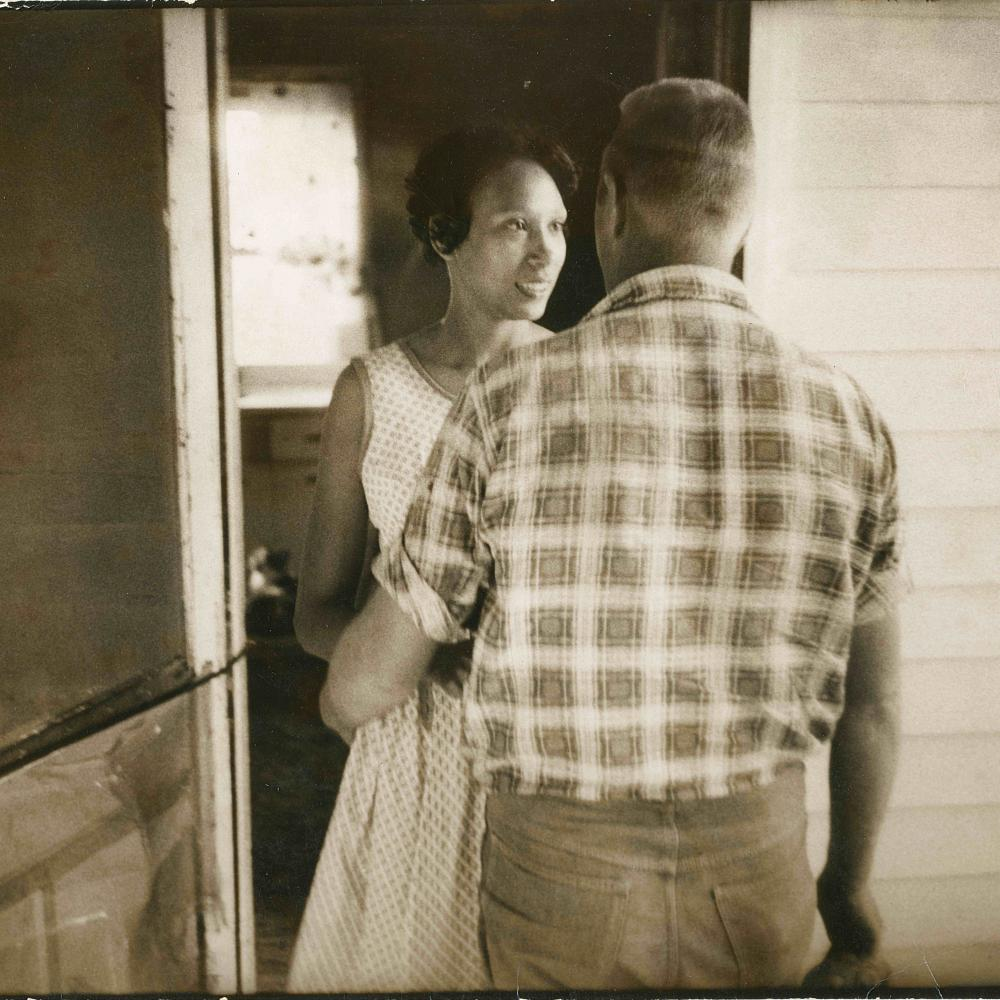 Sepia-colored photo of a man and woman in a doorway.