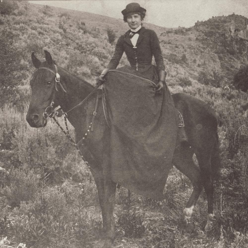 Black and white photo of a woman riding a black horse, wearing a full dress and hat.