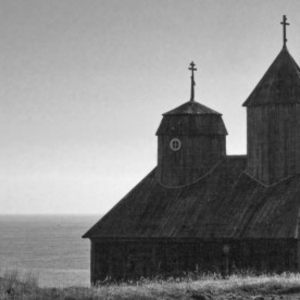 Black and white photo portrait of a seaside church with two cupolas.