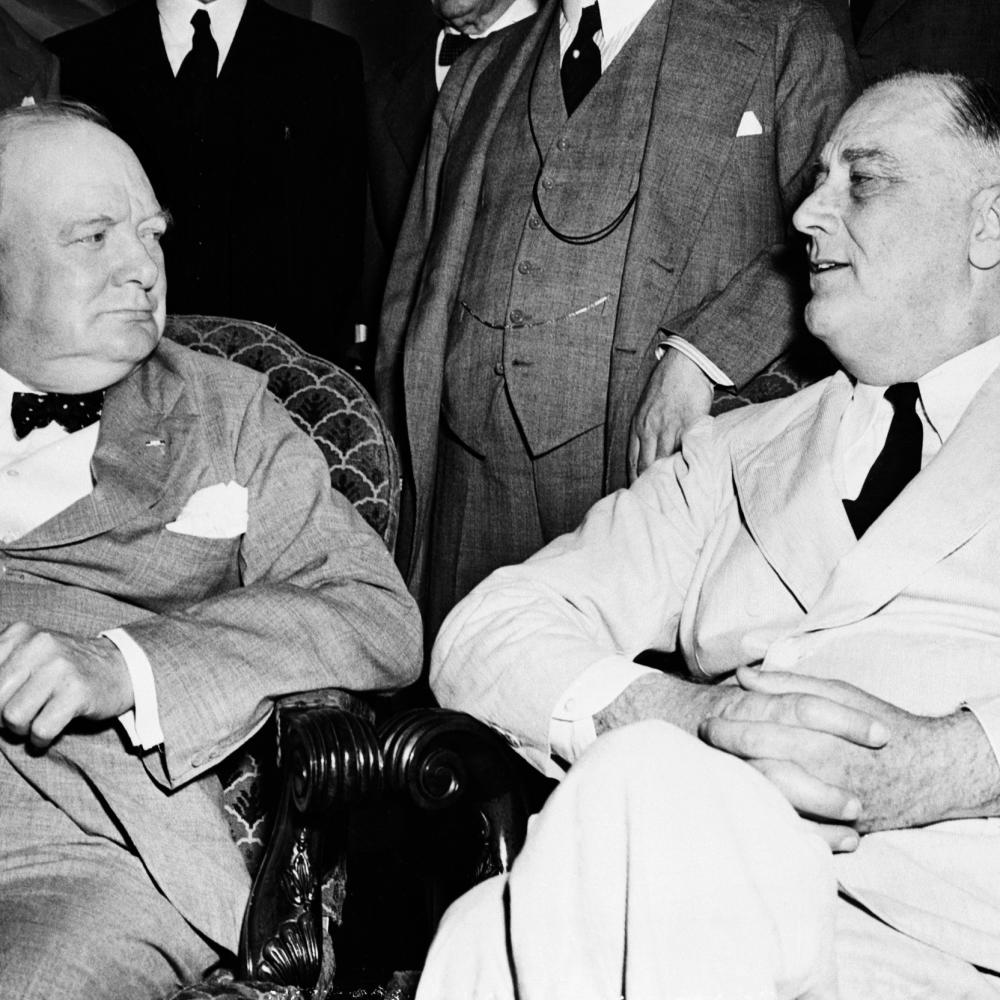 Black and white photo of Winston Churchill and Franklin D. Roosevelt sitting together.