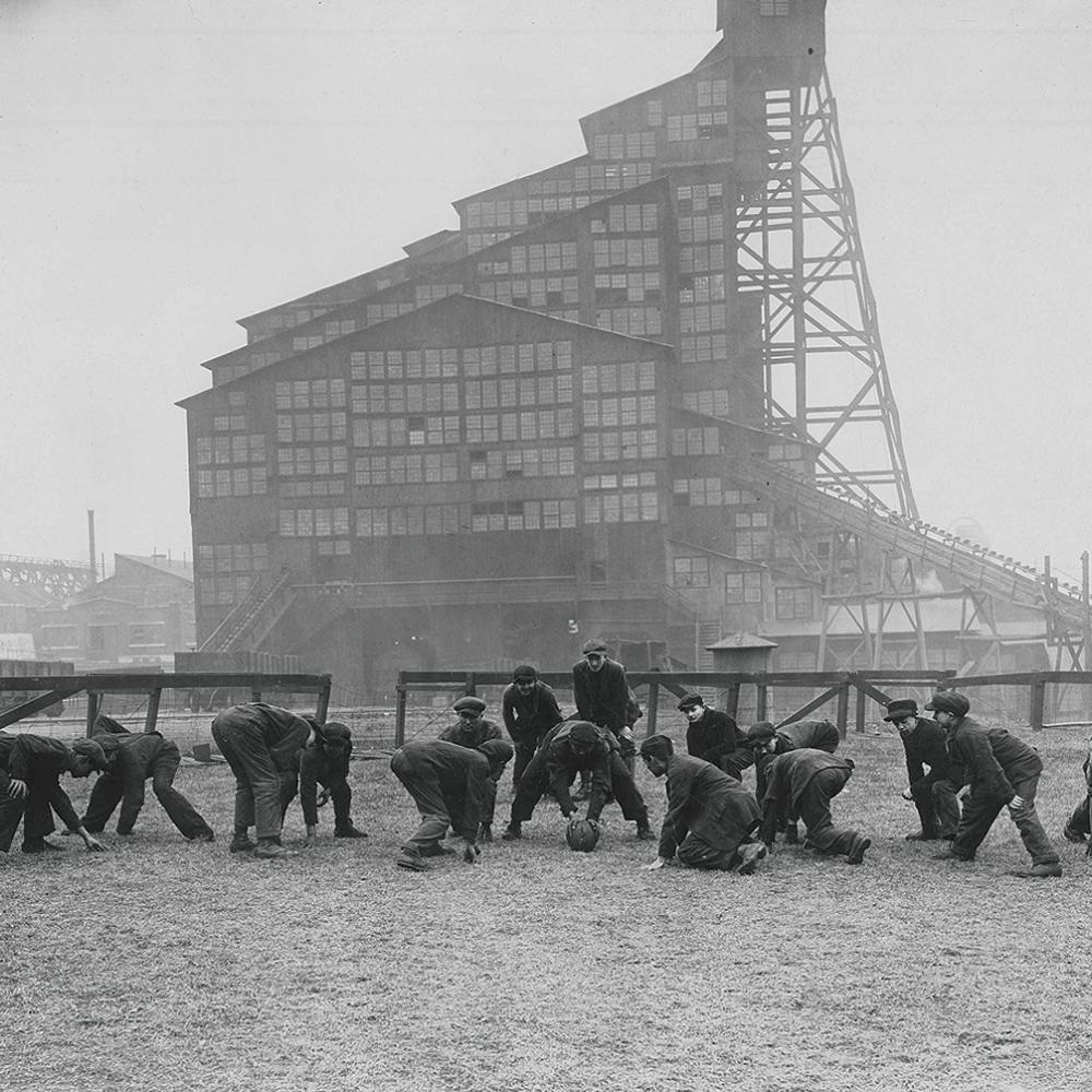 Black and white photo of boys playing football with a mining facility in the background.