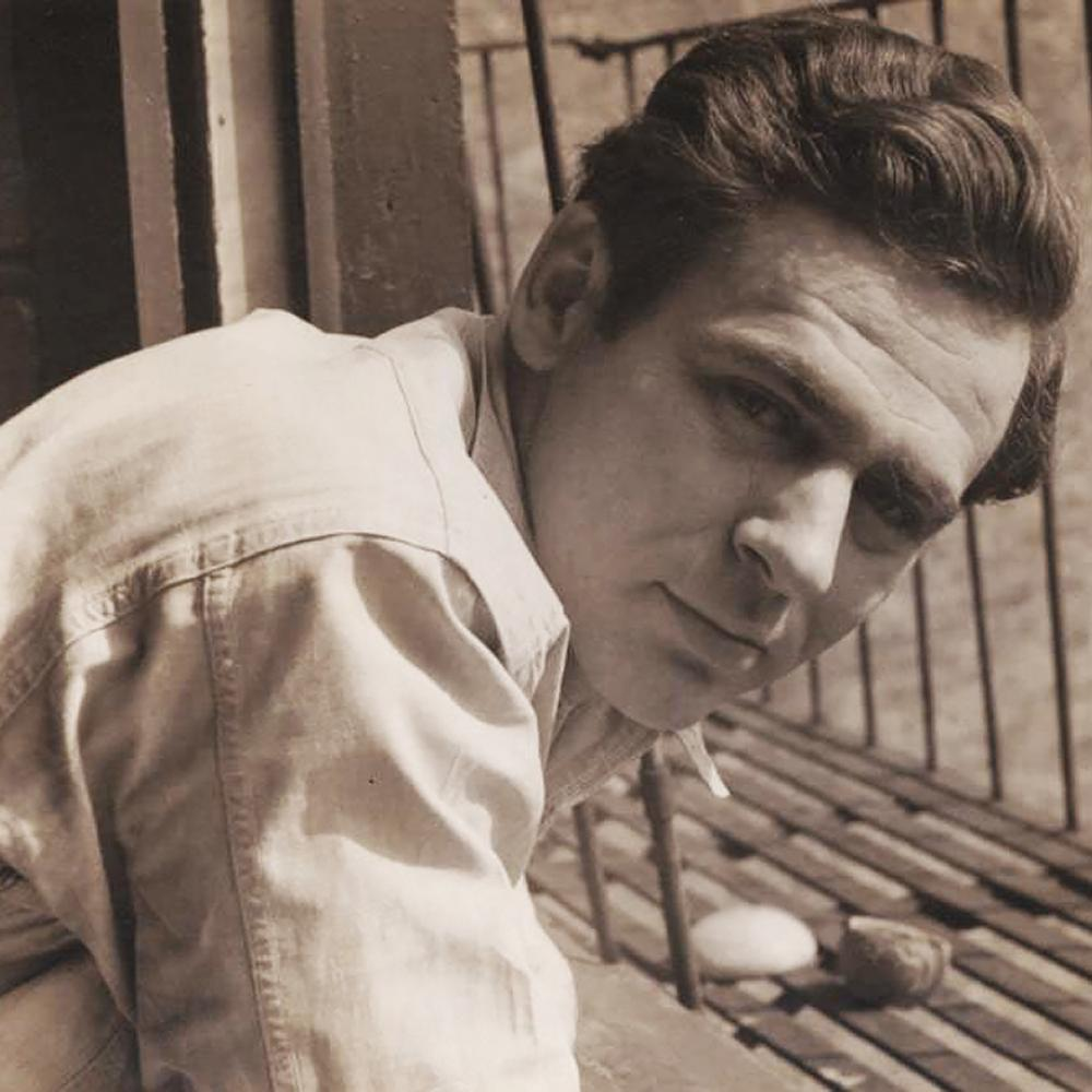 Sepia-colored photo portrait of James Agee leaning in at an angle.