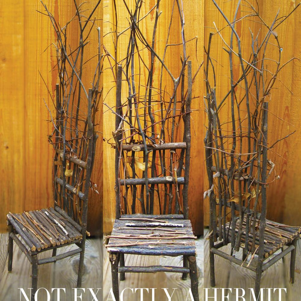"Photo of three chairs made of tree branches with a plywood background and the text ""Not Exactly a Hermit"" written at the bottom."