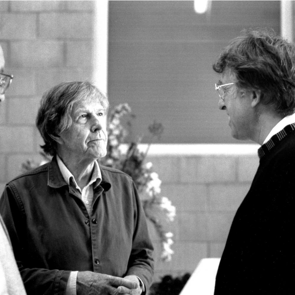 Black and white photo of John Cage meeting with another man.