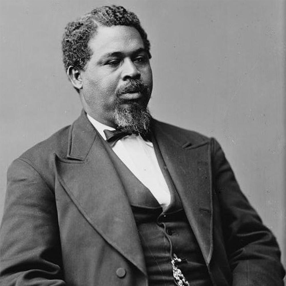 Black and white photo portrait of Robert Smalls wearing a suit and sitting down.