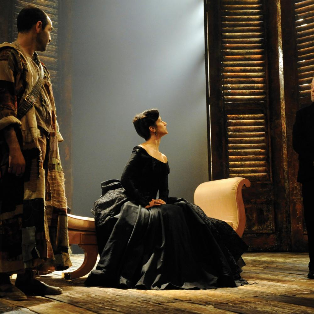 Female actor in a black velvet dress, seated, looks defiantly at the male actor in a dark suit, during a scene of Twelfth Night