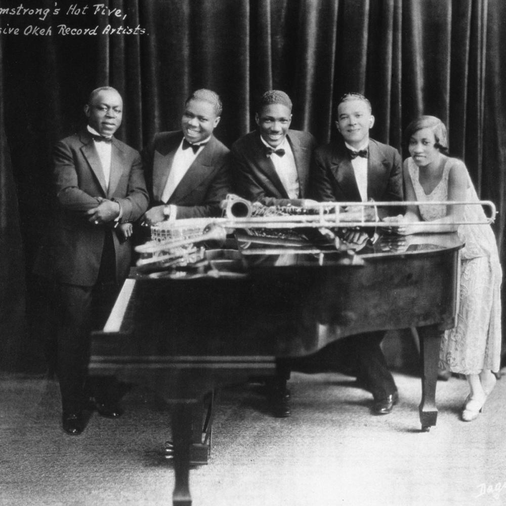 The hot five pose around a grand piano