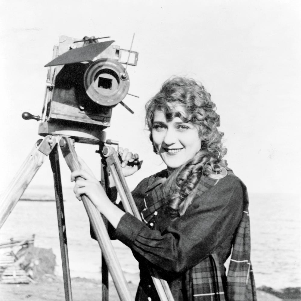 Pickford in a plaid coat, standing with one of her cameras and smiling at the camera