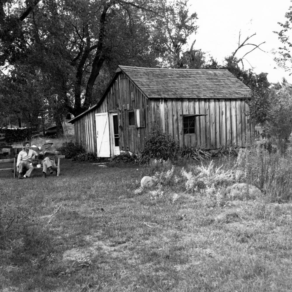 Black and white photo of two men on a bench outside a shack
