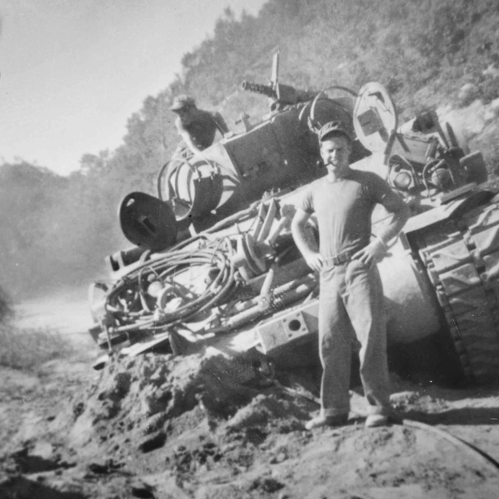 McInroe stands with his hands on his hips, pipe in his mouth, in front of his tank