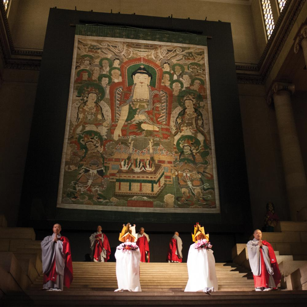 The Śākyamuni Assembly, hanging on a stage, with monks performing in front of it