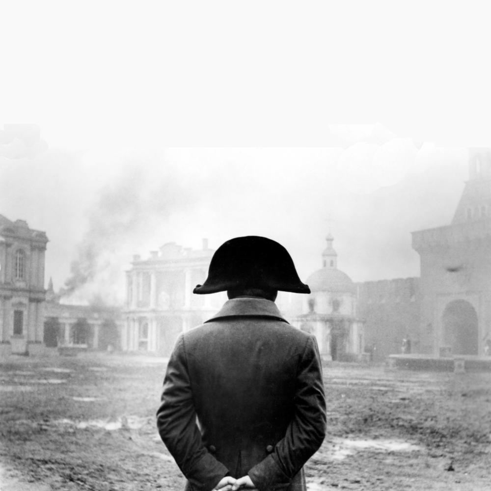 Black and white photo of Napoleon facing away from the camera, down-range, beholding a city plaza.