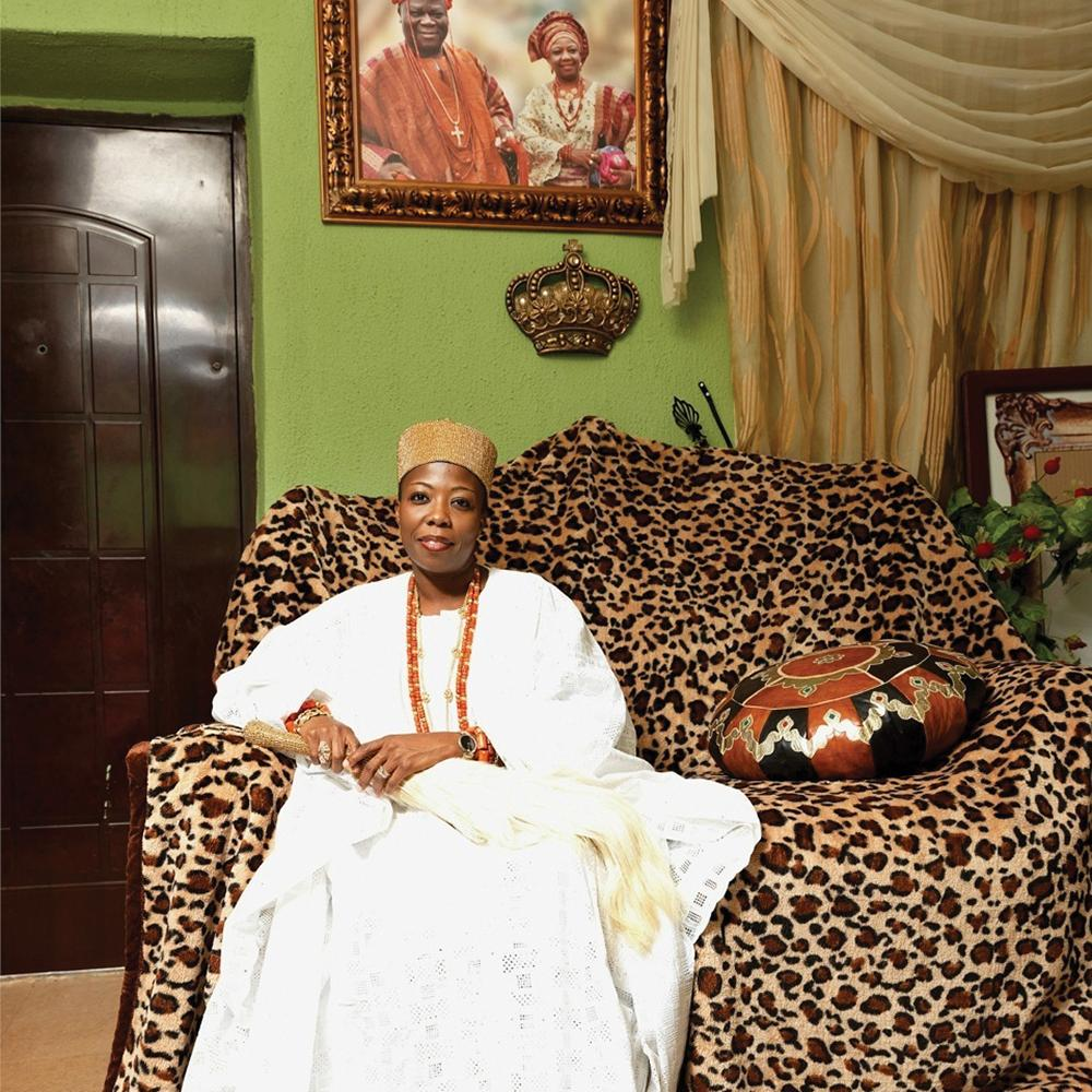 HRM Princess Dr. Adetutu Adebiyi Adesida, seated on a leopard print couch, wearing a write dress