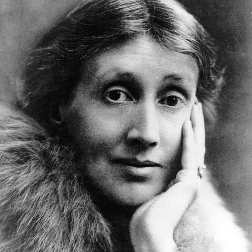 Headshot of Virginia Woolf, with her hair in a low bun, wearing a fur stole, and cradling her chin in her hand