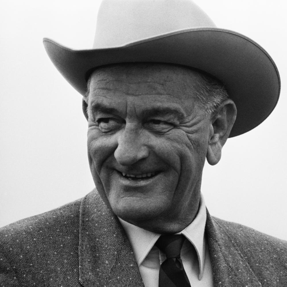Black and white photo of a man in a suit smiling.