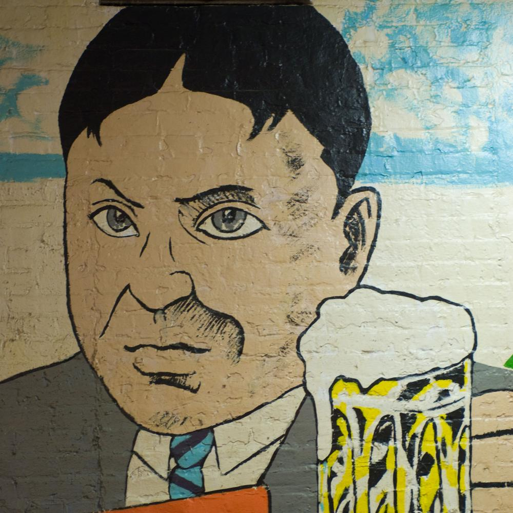 mural painting of a man in a suit holding up a beer