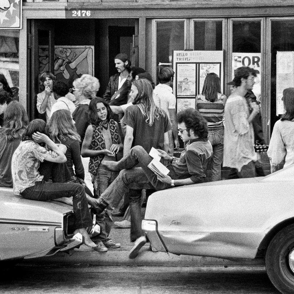 Black and white photograph of people standing around and lounging on cars