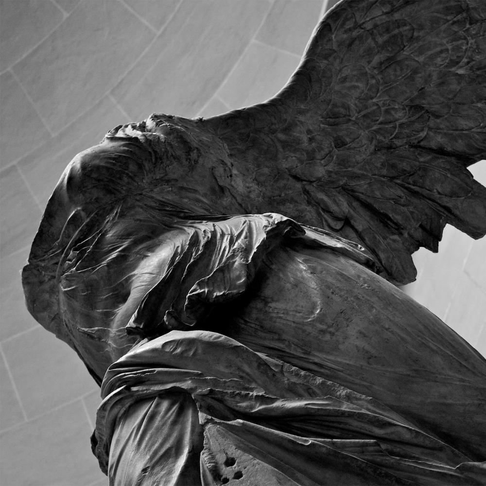 Black and white photo of a winged statue with no head.
