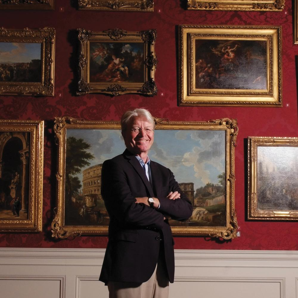 Color photo of Gary Vikan standing before a wall of paintings. He wears a black blazer and khaki dress pants.