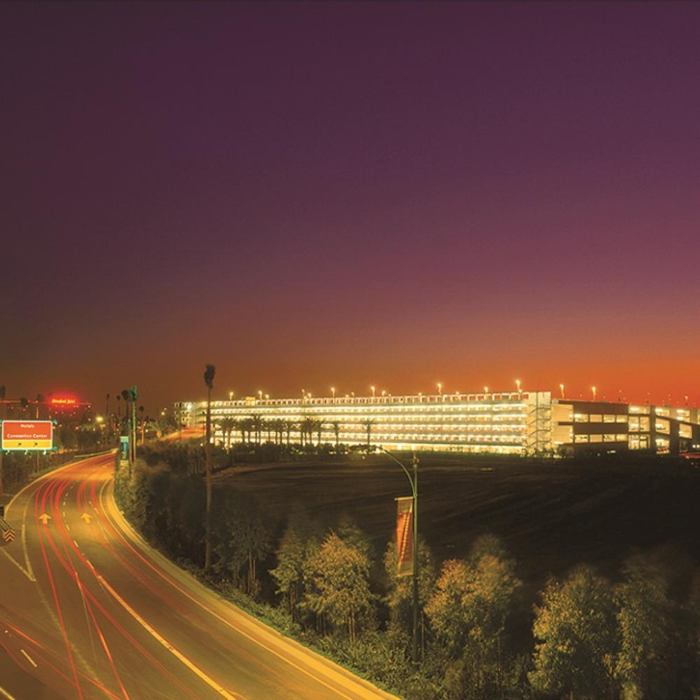 Photograph of a parking structure in distance, highway in foreground, at sunset