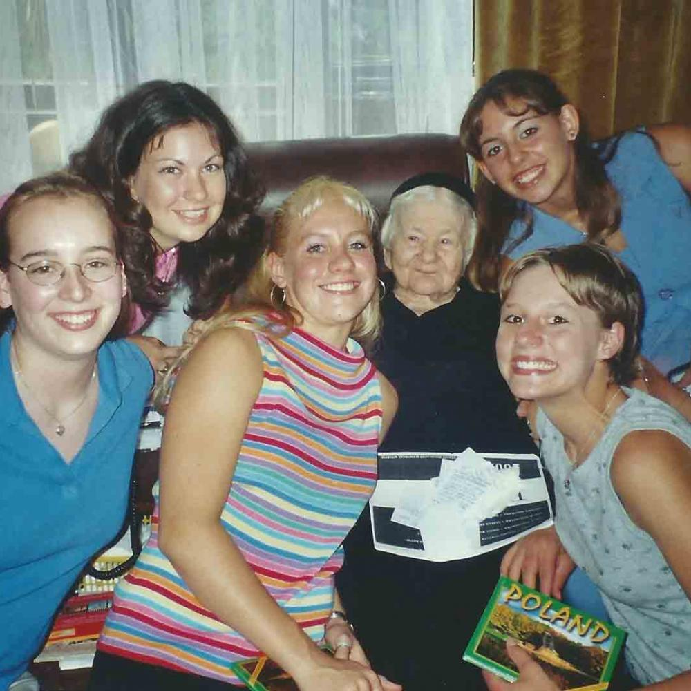 Group photo of Sendler and the girls from Life in a Jar, 2002. Sendler is sitting in a brown leather sofa with the girls surrounding her.