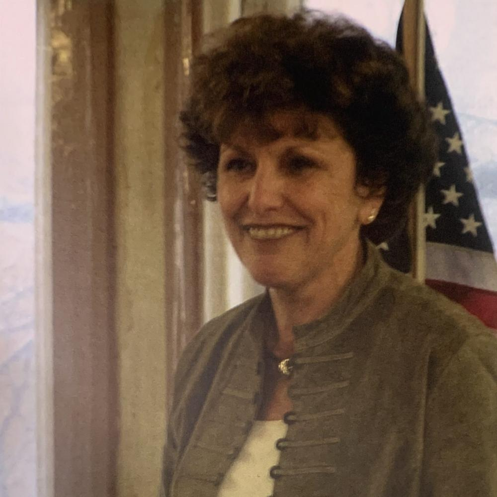 Portrait of Jan Fedewa standing at a podium with a US flag in the background. She is in a light brown, unbutton shirt jacket with a white shirt.