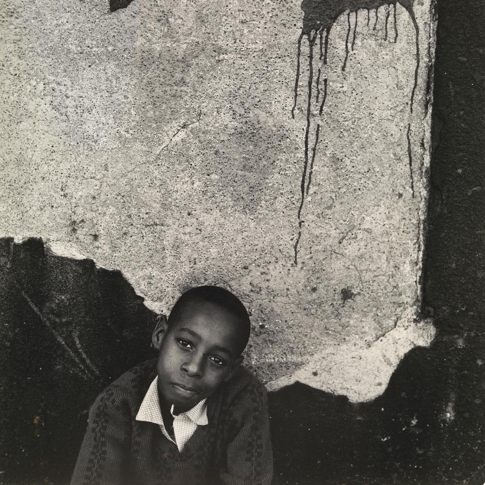 photo of a young a boy around nine years old posing before a cracked cement wall