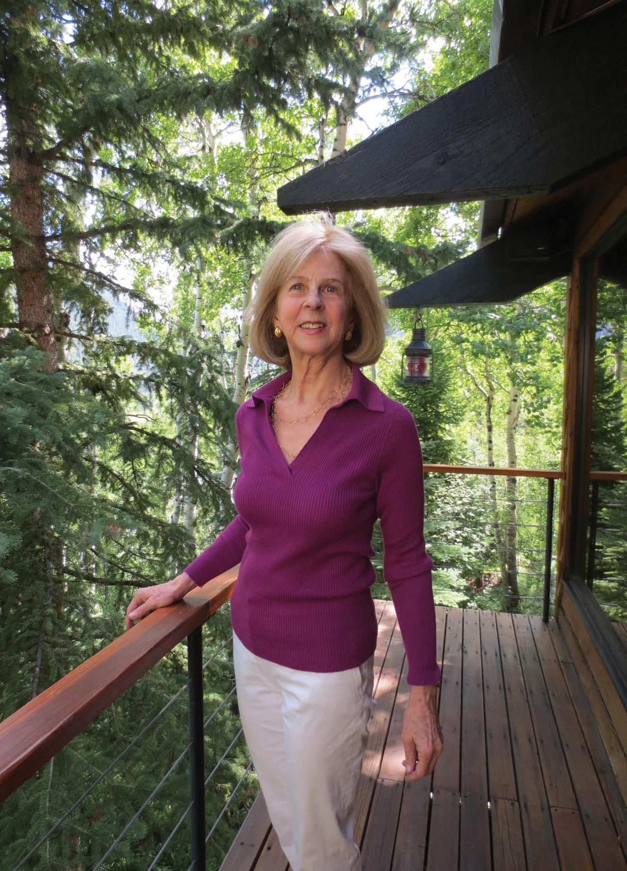 Elaine Pagels on a balcony, surrounded by forest
