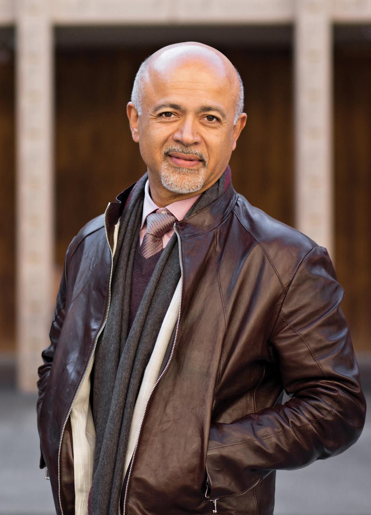 Abraham Verghese, in a leather jacket with his hands in his pockets