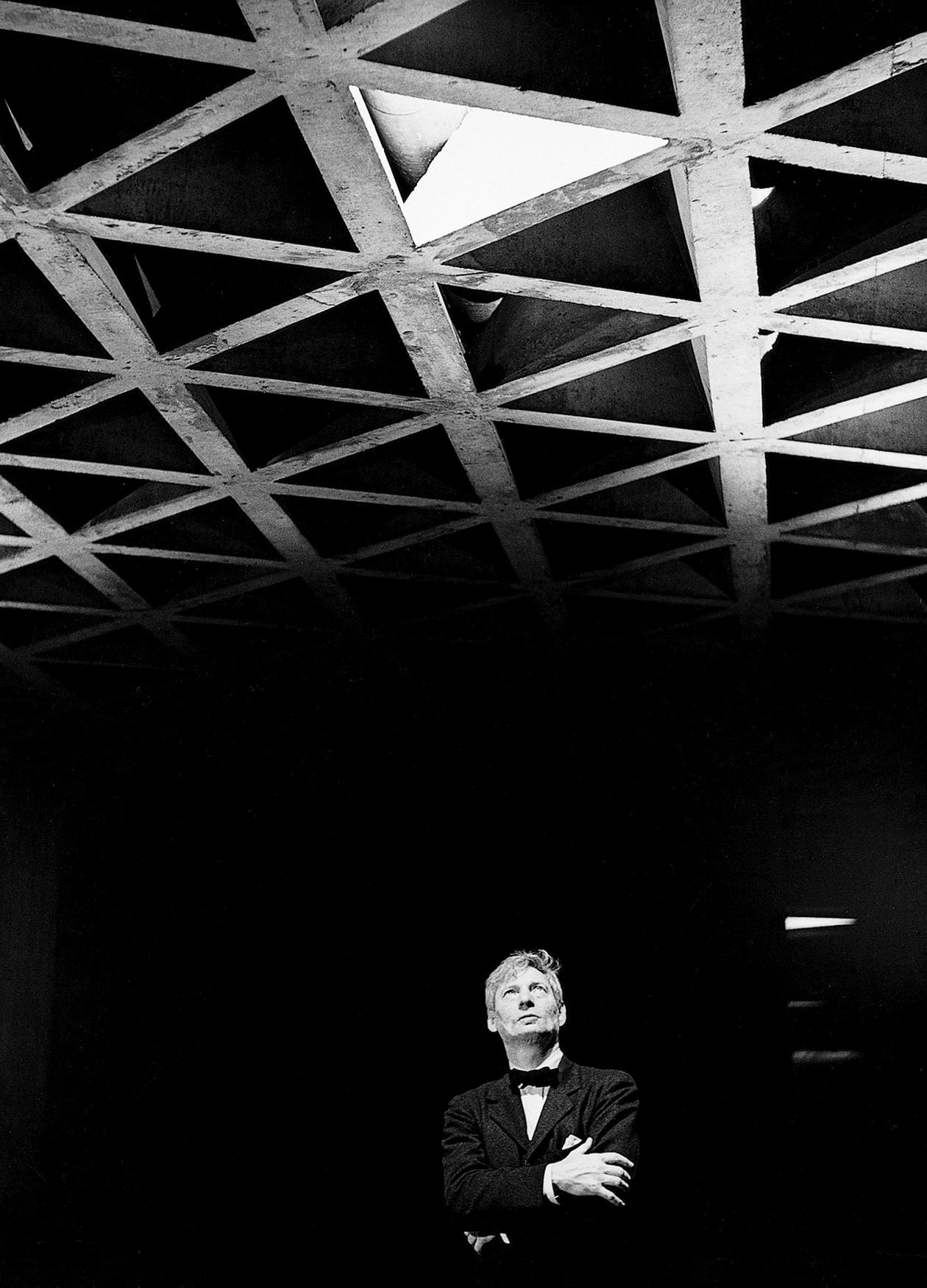 Black and white photo of Louis Kahn standing in a dark room, looking at a decorative ceiling.