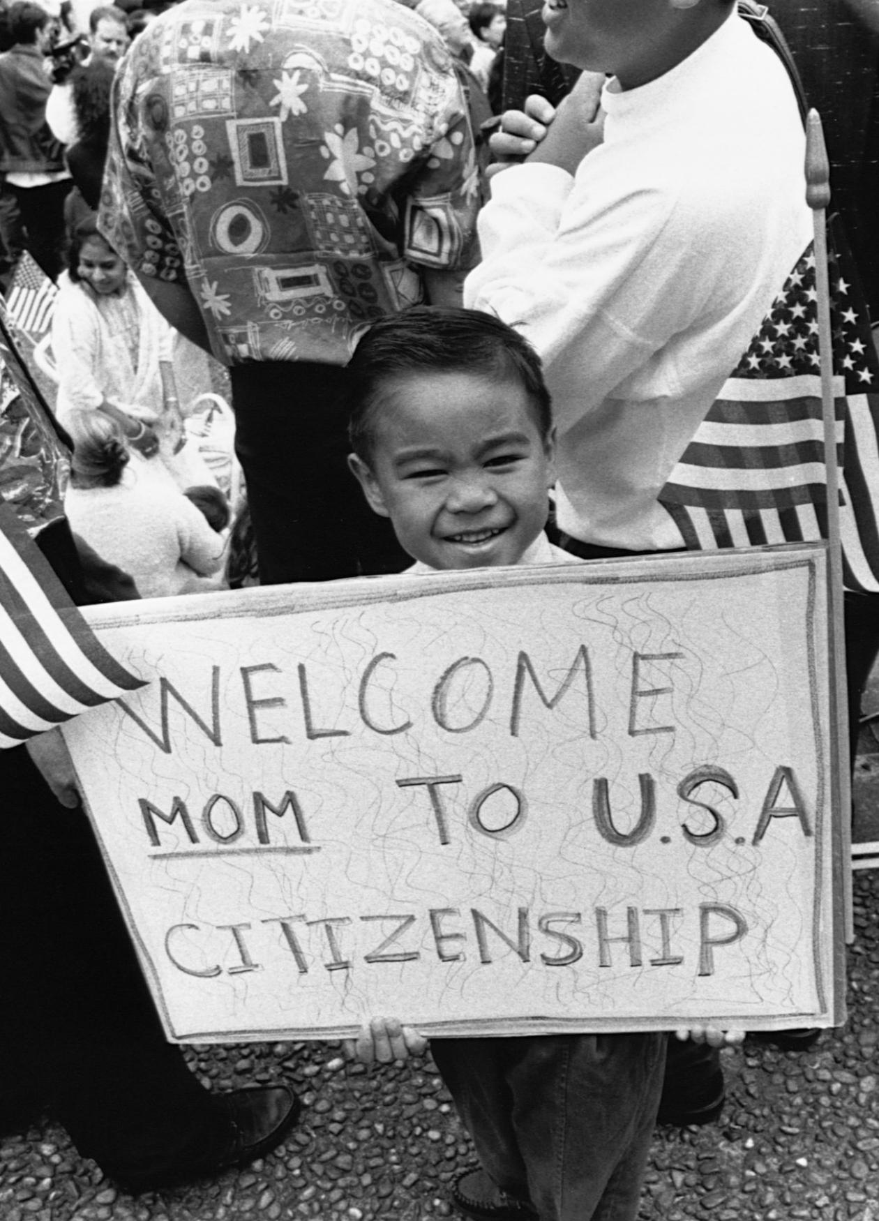 "A young boy holds up a sign, flanked by American flags, that reads ""Welcome Mom to USA citizenship"""