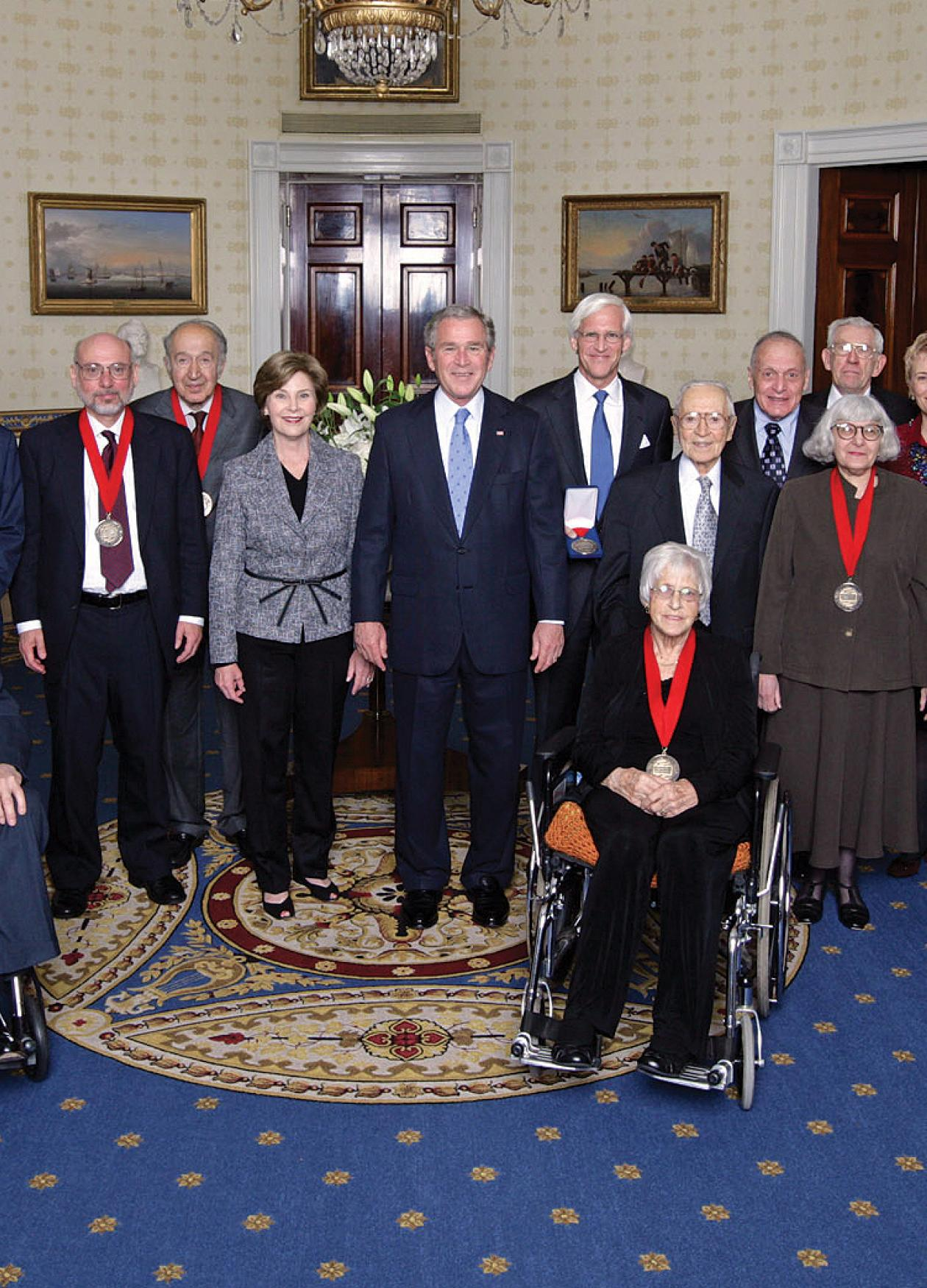 President Bush, standing in the middle of the Medalists wearing their medals, in the Oval Office