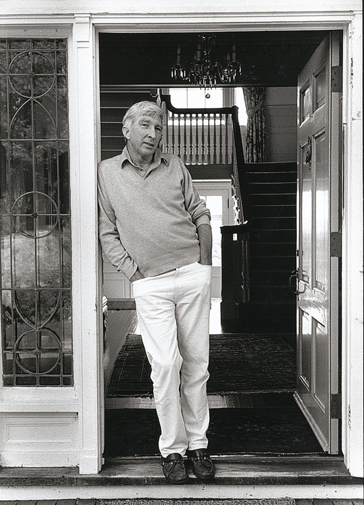 Black and white photo of man leaning against doorway