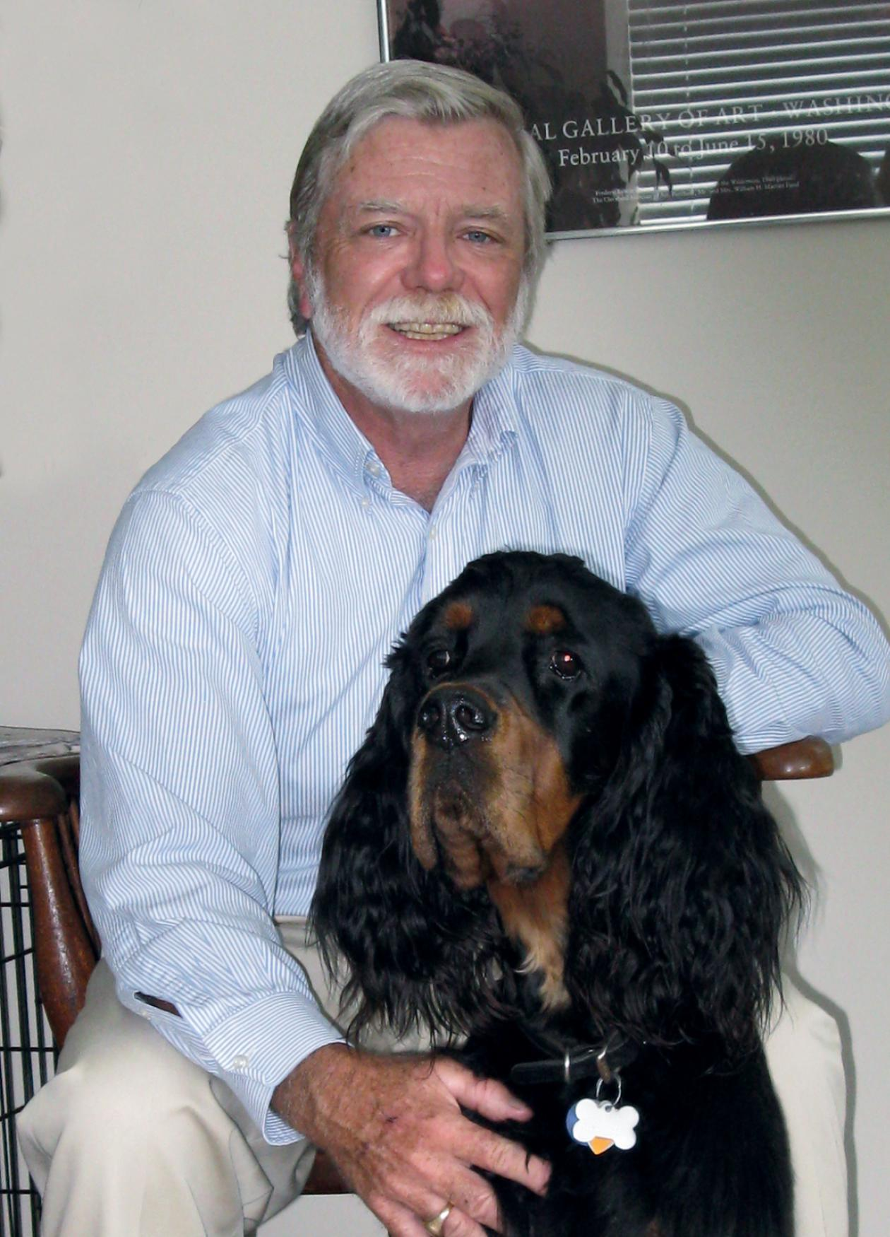 Photograph of man sitting down with dog
