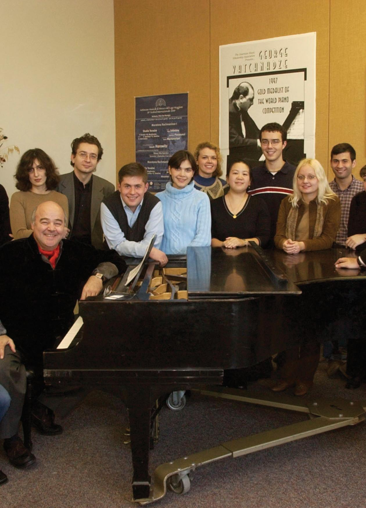 Group photo of musicians standing around a piano