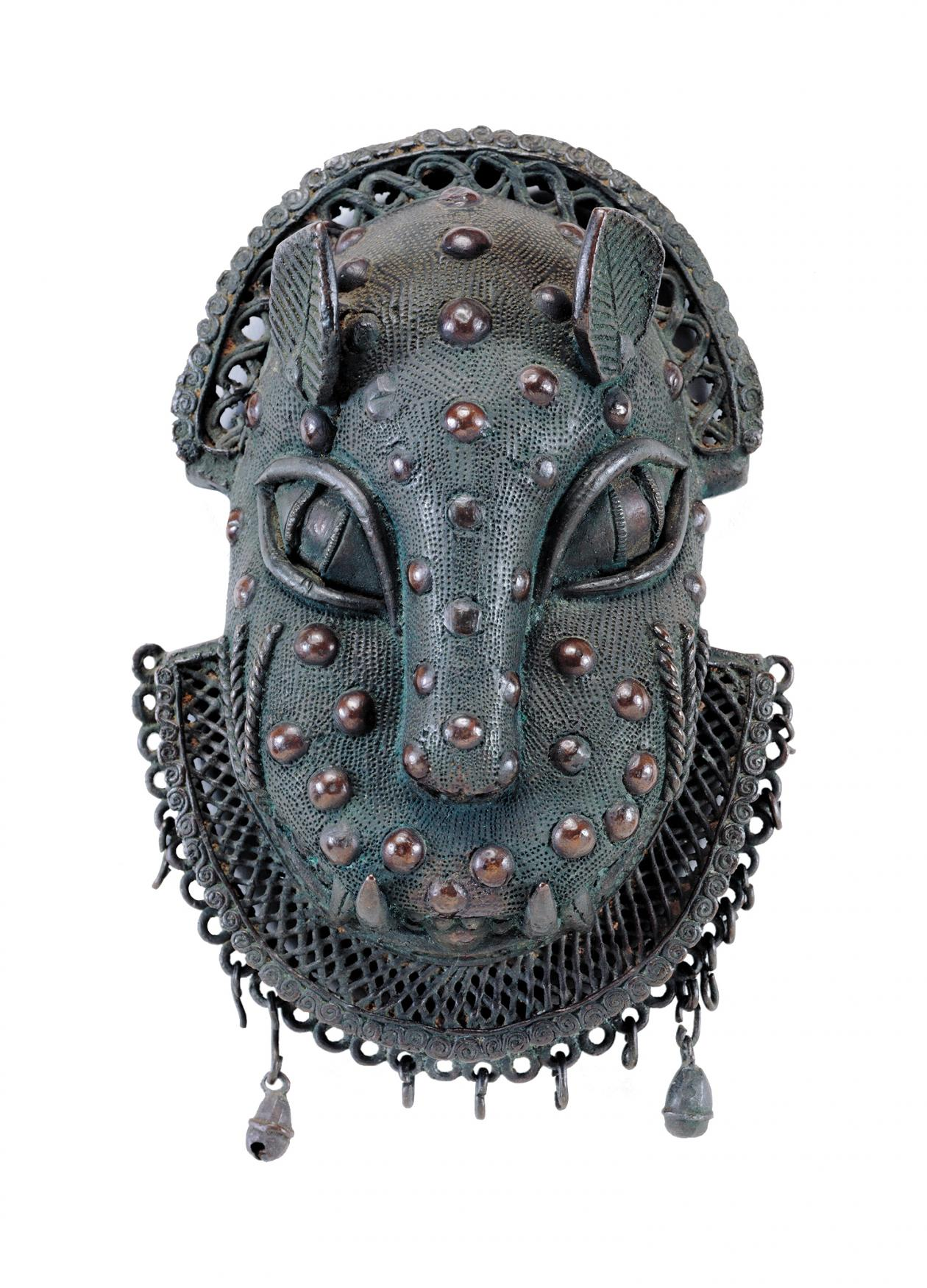 Blue green brass ornament in the shape of a leopard head, with brass studs decorating the face