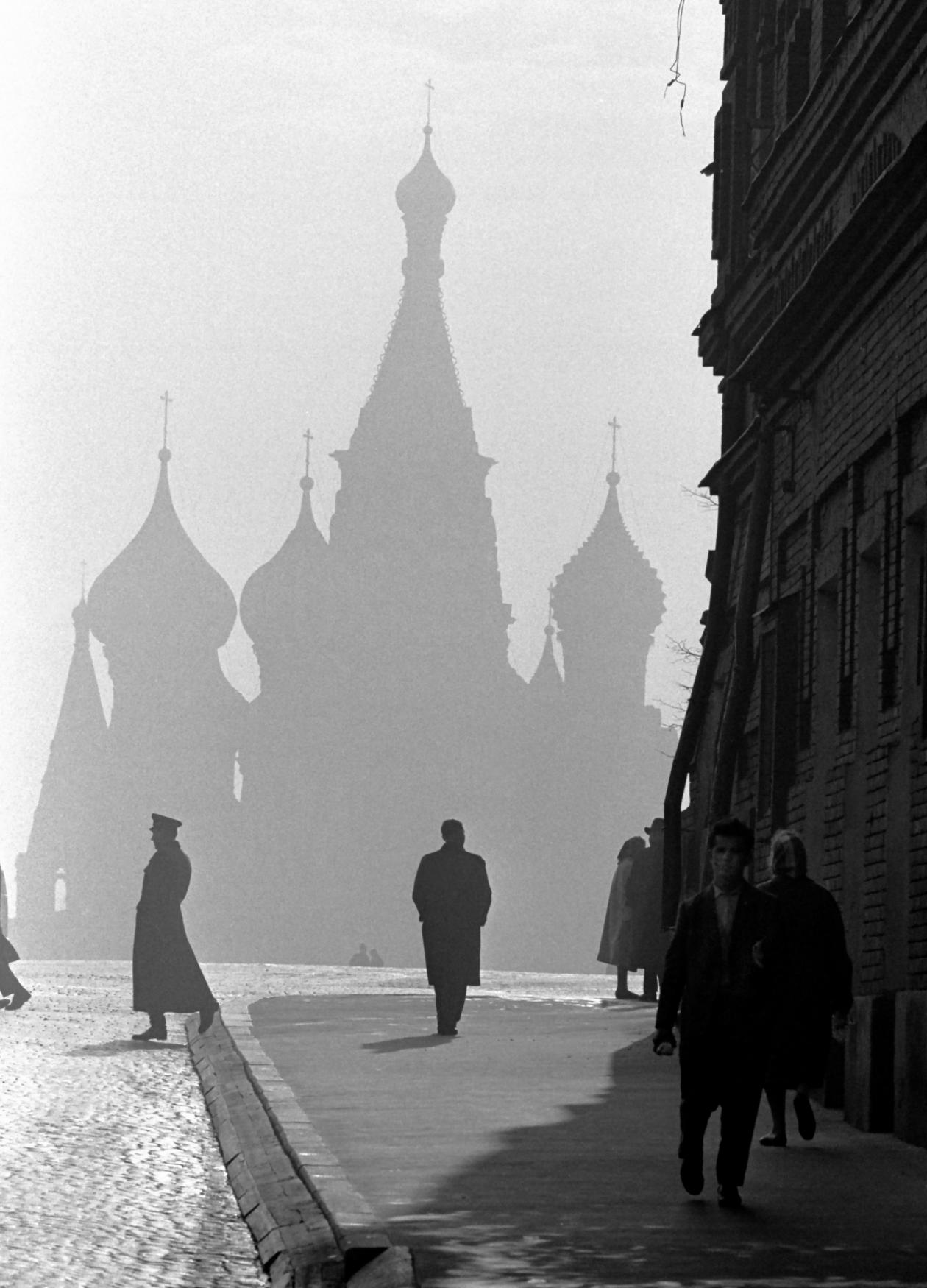 A few people walk on a wide sidewalk, with the shadow of the kremlin rising through the mist in the background